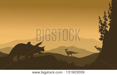 Parasaurolophus and Triceratops in hills of silhouette at morning