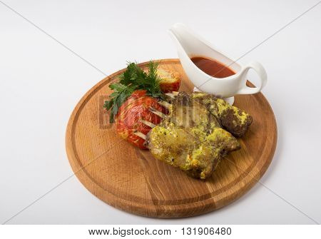 Grilled mutton ribs served with ketchup on wooden board