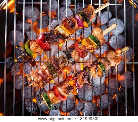 Grill with meat skewers shot from above view