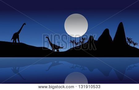Silhouette of Brachiosaurus in riverbank at the night