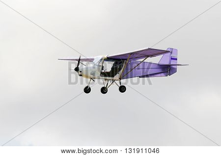 Flying private propeller-driven airplane over gray cloudy sky