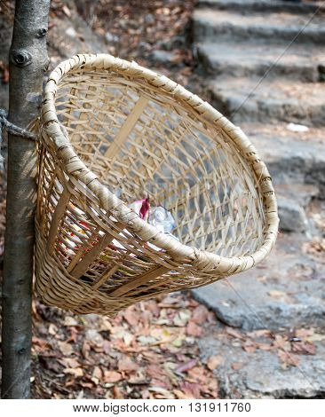 Unique handmande bamboo basket or dustbin placed on the streets of rural Nepalese Village.