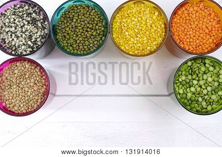 Multicolored clear glasses with various legumes ( green peas red lentils canadian lentils indian lentils black lentils green lentils green mung beans) on white wooden background