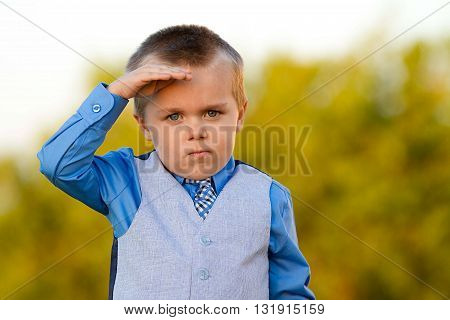 Boy in a suit and tie pretending to be professional saluting