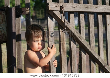 Baby Girl Near Fence Outdoor At Summer With Bronze Tan