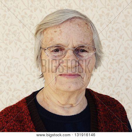 Grandma's portrait against vintage patterned wall -
