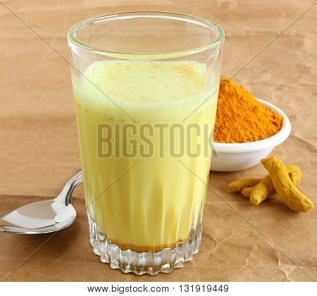 Healthy drink turmeric latte and turmeric powder and root.