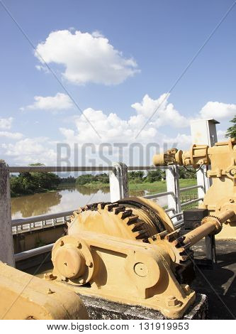 Mechanical closing the sluice on cloud and blue sky