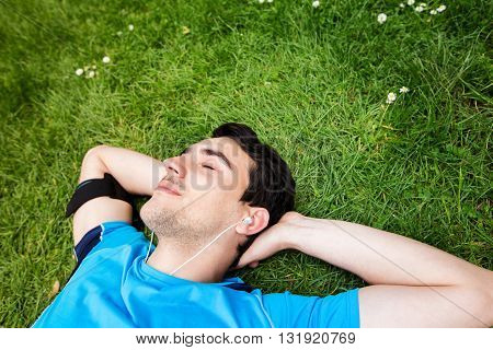 Sport fitness man relaxing listening to music after training outdoor in a city park . Young male athlete resting relaxing lying on grass after running and training exercise outside in summer.