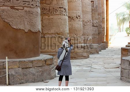 Tourist capturing photo at Al Karnak temple in Luxor, Egypt
