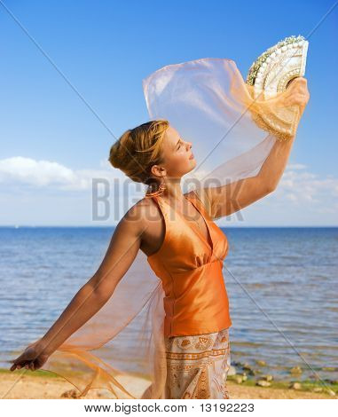 Beautiful redhead girl on the beach at sunny day