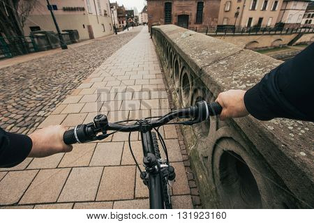 Close-up image of cyclist man hands on handlebar riding bike in city street face is not visible.Young man riding bike in city bridge near river.View from bikers eyes.