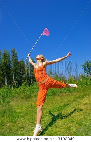 Beautiful girl with a butterfly net jumping on a meadow