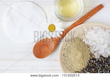 Ingredients homemade facial mask. Lavender herb, salt, cosmetic clay, base oil, fresh chamomile flower. Top view white wooden background.