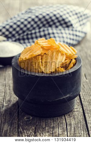Crinkle cut potato chips on kitchen table. Tasty spicy potato chips in bowl.