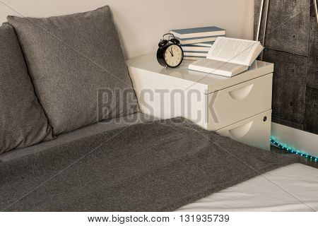Shot of a grey-covered bed and a white nightstand in a modern bedroom