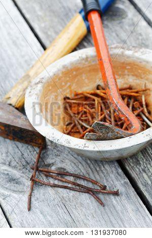 rusty nails and nail puller close-up on board