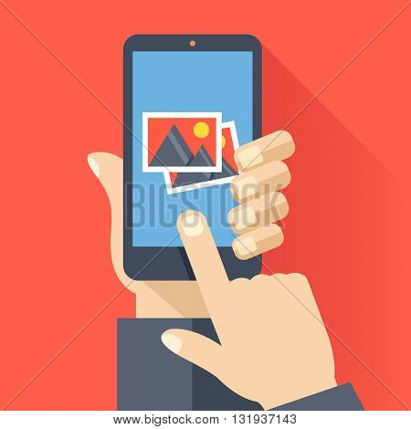 Hand holds smartphone with photos icon on smartphone screen. Multimedia, photo album app concept. Modern simple flat design for web banners, web site, infographics. Creative vector illustration