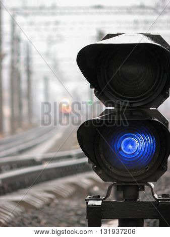 Railway traffic light shows blue signal on railway. Blue light. Moving train with lights and green railway traffic light are on the background.