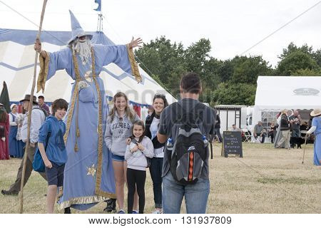 TEWKESBURY, GLOC. UK-12 JULY: Wizard on stilts poses with family for a quick photo on 12 July 2014 at Tewkesbury Medieval Festival, UK