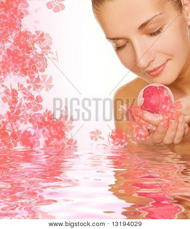 Beautiful girl with aroma bath ball in rendered water