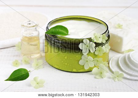Fresh plant-based cosmetic. White skincare cream in cosmetic container, fresh flowers plant leaves, essential oil, cotton pads.