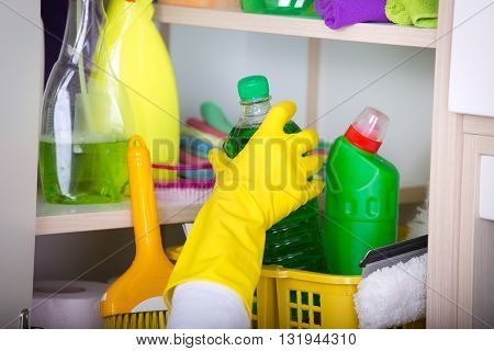 Woman Storing Cleaning Tools In Pantry