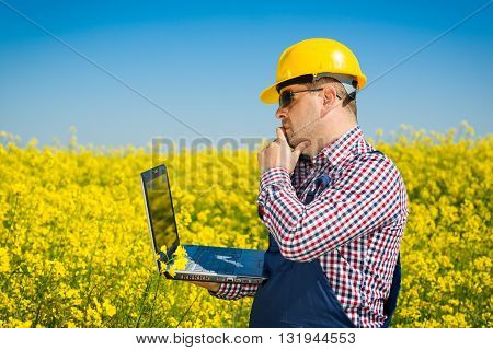 Worker in a rapeseed field doing inspection for biodiesel production