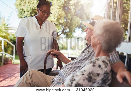 Female home caregiver looking after senior couple relaxing on a bench outside their retirement home.