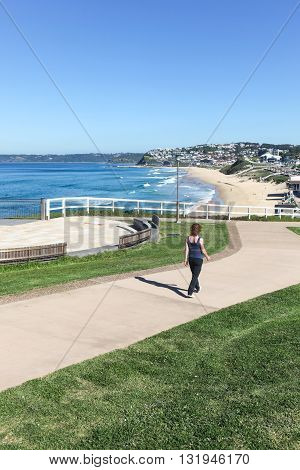 A woman walks along newly constructed coastal walkway at Bar Beach - Newcastle Australia and a beuatiful sunny Autumn day.