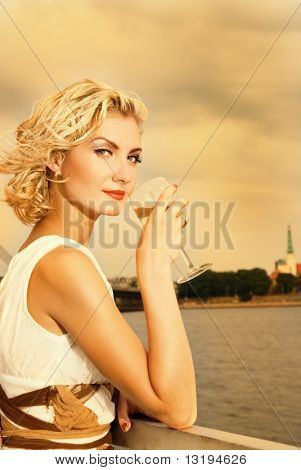 Beautiful blond girl drinks champagne near the river at sunset time poster