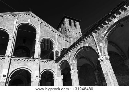 Milan (Lombardy Italy): the medieval church of Sant'Ambrogio in Romanesque style. Facade and portico. Black and white