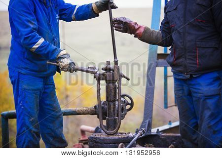Oil workers check oil pump. Roustabouts doing dirty and dangerous work on an oil well servicing rig.