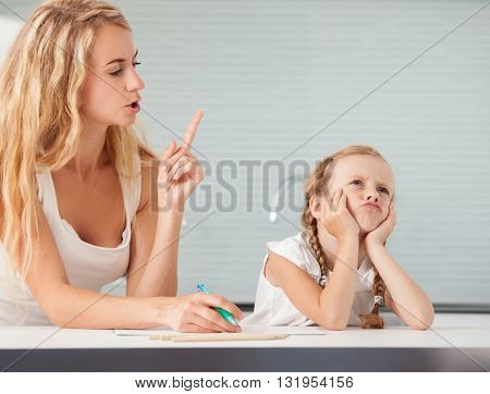 Parent helps the child to do homework. Sad girl. Mother swears her daughter