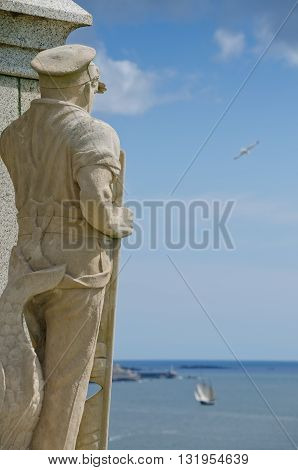 PLYMOUTH HOE, ENGLAND. 22nd May 2016. A carved figure on the memorial to the Plymouth division Royal Marines overlooks Plymouth Sound on one of this Spring's first sunny days.