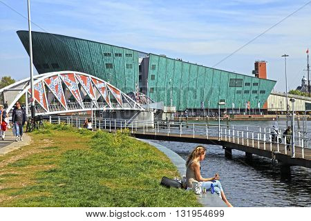 AMSTERDAM, NETHERLANDS - MAY 6, 2016: People on embankment near Science Center NEMO designed by Renzo Piano (1997) - science educational museum knowledge institute and center of tourism in Amsterdam, Netherlands.
