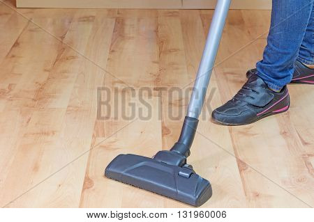 Woman is cleaning laminate flooring by vacuum cleaner.