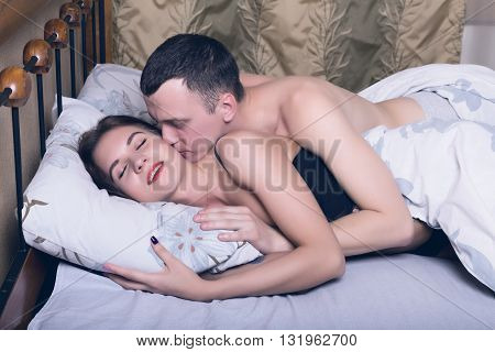 propitiation of men and women, young couple asleep in bed in an embrace. Problem of relations between men and women.