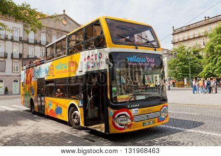 PORTO PORTUGAL - MAY 26 2016: Yellow Bus on Liberdade Square in the historical center of Porto Portugal (UNESCO site). Yellow Bus provides two lines of city sightseeing tours around main attraction of the city and suburbs