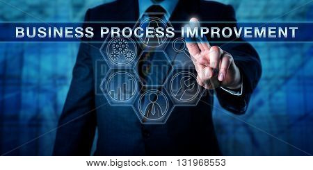Administrator pushing BUSINESS PROCESS IMPROVEMENT on a virtual transparent control screen. Business concept and process management metaphor for a methodology aimed at achieving efficient results.