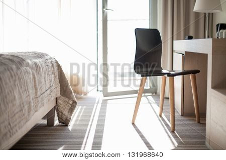 Bright, neutral and minimal hotel room with a balcony