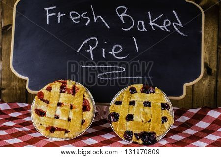 two pies on checked table cloth in front of chalkboard advertising fresh baked pies