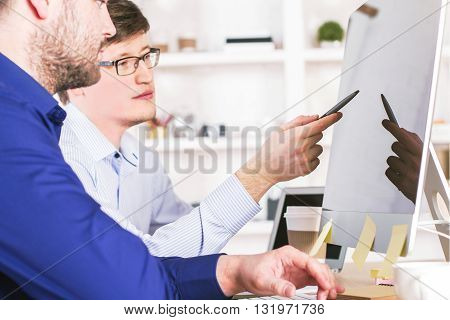 Businessmen in office looking at blank computer monitor and discussing something