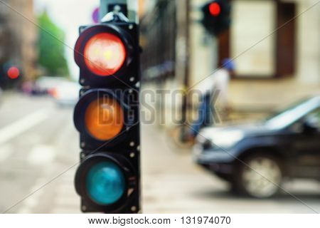Traffic lights at the crossroads of the city and the car on a background of a passing cyclist. Blurry