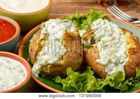 Jacket potatoes served with tzatziki sauce. Close-up.