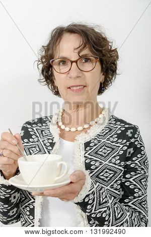 a beautiful mature woman drinking cup of tea
