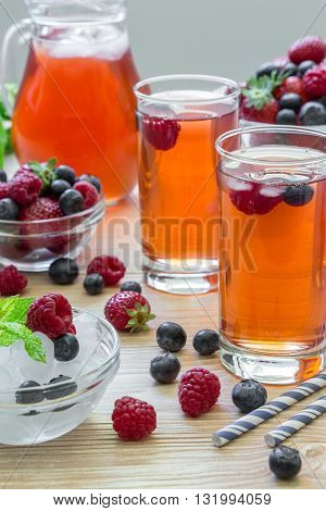 2 compotes of raspberries strawberries blueberries near bowl of ice 2 bowls with berries mint leaves carafe compote straws on light background scattered berries. Berries compote. Vertical.