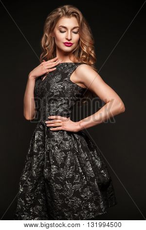 Portrait of young beautiful model with pink lips posing in elegant dress while looking down.Studio shot