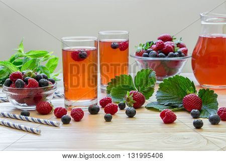 Left two glasses of berries compote near 2 bowls with berries mint carafe compote on a light wooden background scattered berries and empty space. Fresh berries compote and empty space. Horizontal.