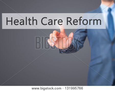 Health Care Reform - Businessman Hand Pressing Button On Touch Screen Interface.